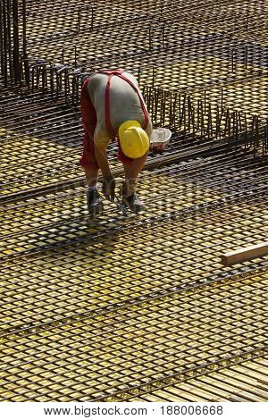 Construction worker between steel bars fixing armature on construction site