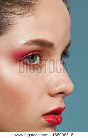 Close up portrait of young beautiful brunette girl with bright make up.