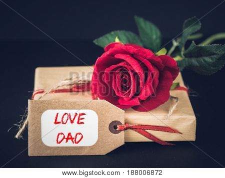 Father's day concept. LOVE DAD message with red rose on black background