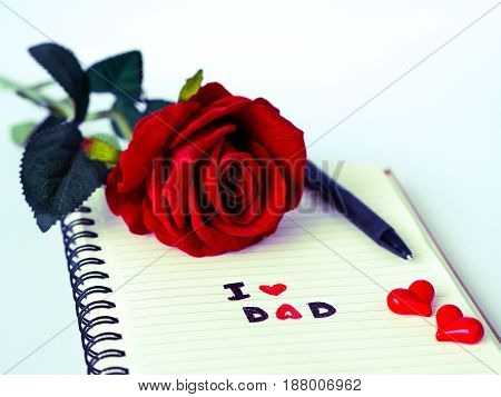 Father's day concept. I LOVE DAD message write on note book with red rose and pen on white background