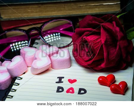 Father's day concept. I LOVE DAD message write on note book with red rose stack of books glasses and sweet marshmallow in the shape of heart on dark background