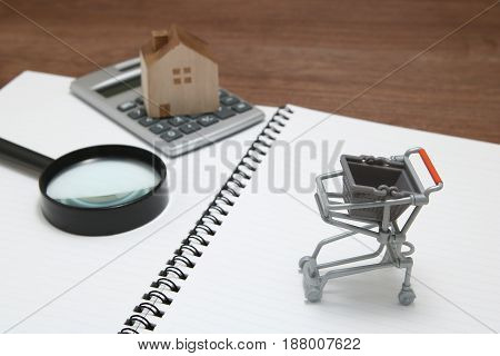 Shopping cart. Buying new house, real estate and home mortgage concept.