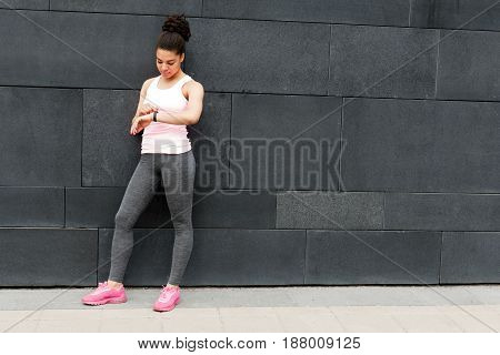 Young woman standing at wall, checking activity tracker