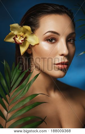 Side shot of attractive woman with beautiful flower in hair. Standing behind fresh exotic flowers.