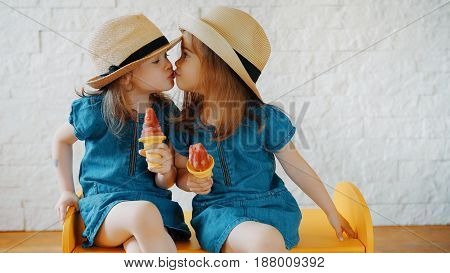 Two little girls give themselves kisses and wait for summer holidays