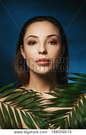 Vertical shot of amazing woman with wet slocked back hair. Covering shoulders with leaves.