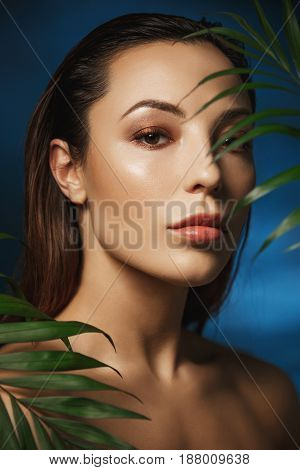 Closeup of gorgeous woman with beautiful fresh make up. Behind green leaves. Fashion photography.