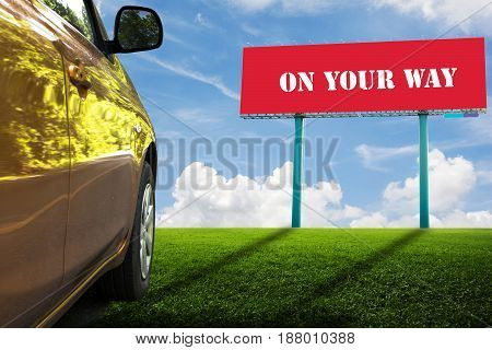 Red billboards on green field and Orange car. ON YOUR WAY