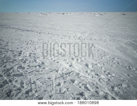 Beach in winter in Siberia. Snow and ice on the sea to the horizon