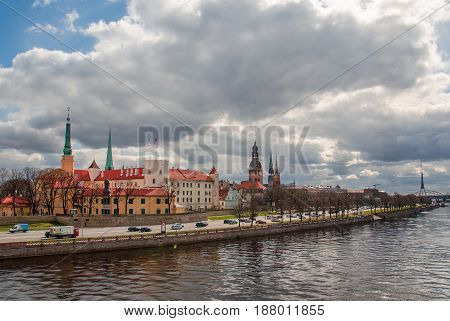 Riga seafront at cloydy day, Daugava promenad, old church towers, medieval castle in front.