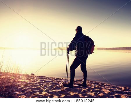 Hiker Man In Dark Sportswear And With Sporty Backpack Standing On The Beach