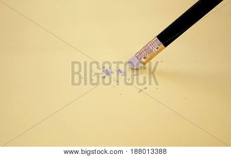 Pencil eraser removing a written mistake on a piece of paper delete correct and mistake concept.