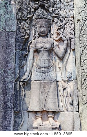 Beautiful Cambodian women dancing Apsaras. Old Khmer art carvings on the wall of Prasat Bayon, the central temple of Angkor Thom Complex, Siem Reap, Cambodia.