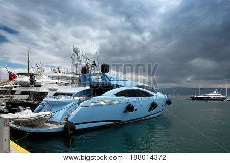 Fast and luxury yacht under a heavy cloudscape at marina Zeas Piraeus Greece