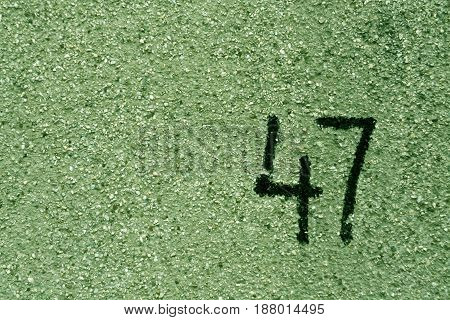 Number Fourty Seven On Green Plaster Wall.