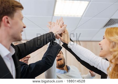 We are the team. Happy positive delighted people laughing and giving the high five while showing their unity