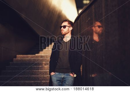 Stylish man in a coat and glasses. Copy space