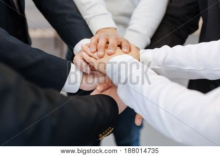 Togetherness and unity. Close up of hands being held together by happy positive people while showing their togetherness