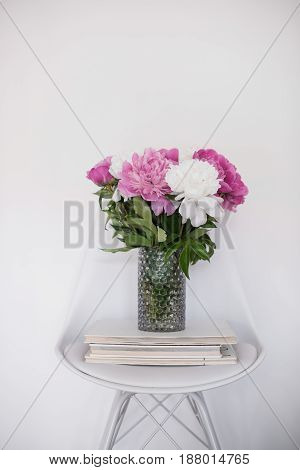 Home flowers decor, bouquet of fresh peonies on designer chair in white room interior