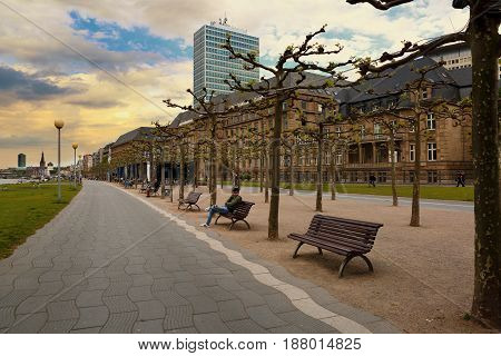 Dusseldorf Germany - May 11 2017: Rhine embankment promenade near the river in the old city center in Dusseldorf in summer dusk time under dramatic bly sky. Old houses and many rest benches along the sidewalk