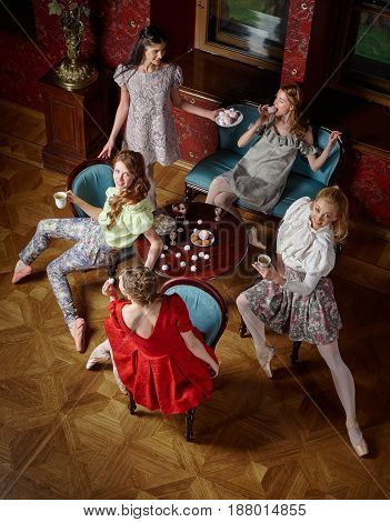 Young caucasian fashion cheerful ballerinas in a pose drinking tea