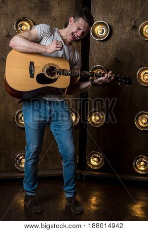 Guitarist, Music. A Young Man Plays An Acoustic Guitar On A Background With Lights Behind Him. Verti