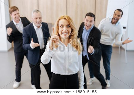 I have an idea. Delighted attractive positive woman standing in front of her colleagues and pointing her finger up while having a new idea