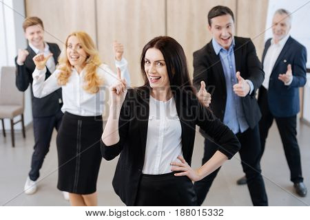 Team of professionals. Beautiful attractive delighted woman smiling and pointing his finger up while having a great team behind her