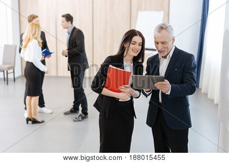 Look at this picture. Nice delighted aged man holding a tablet and showing a picture in it to his colleague while standing with her