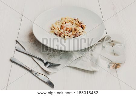 Italian carbonara pasta with bacon, egg yolk and parmesan decorated with basil on white round plate. Restaurant food with fork and knife.