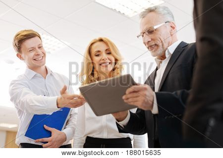 Modern device. Joyful delighted positive colleagues smiling and looking at the tablet screen while standing together