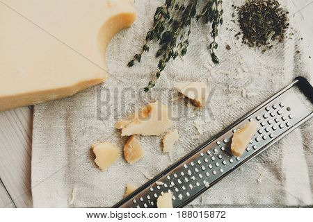 Parmesan piece closeup with small grater. Classic italian cuisine cooking ingredient, grated hard cheese. Top view