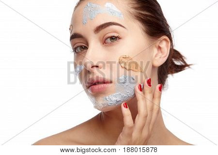Portrait of young model with fresh strokes of cosmetics on face posing sensually on white.