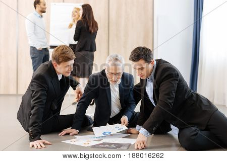 Working together. Nice pleasant positive men sitting on the floor and looking at the papers while working in team