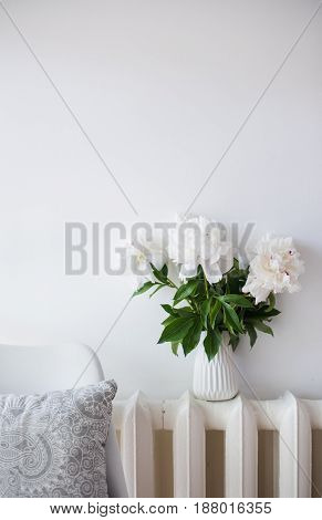 Summer vintage home decoration, bouquet of fresh peonies and designers chair with pillow in white cozy room interior.
