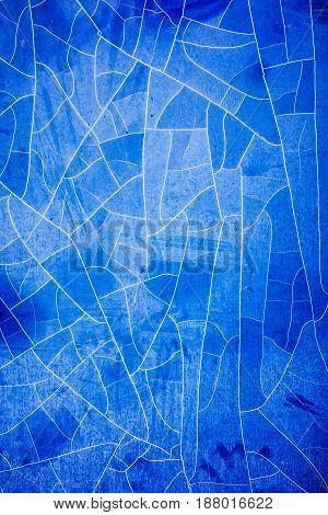 Dirty damaged blue foil on window background.