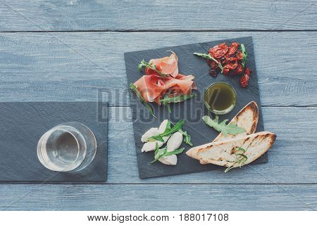 Catering platter antipasto with ham prosciutto, bruschetta bread toasts and mozzarella cheese on stone desk on blue wood table top view with glass of wine