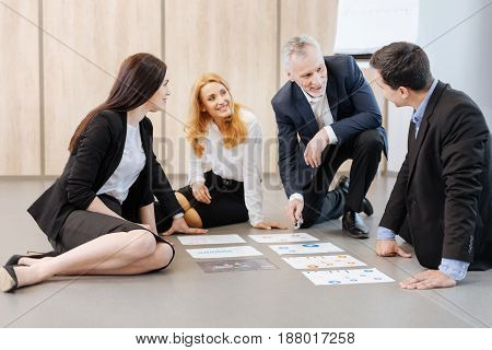 Pleasant communication. Positive friendly delighted colleagues sitting on the floor and having a discussion while working in team