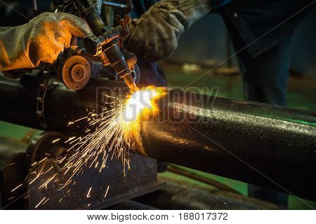 Acetylene torch cutting tube industrial for construction fabrication with bright sparks in steel factory.