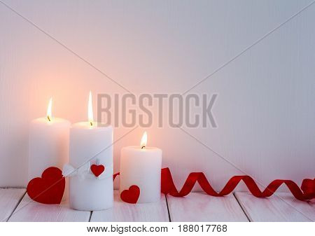 Composition with candles candles heart on white wooden background. Valentines day.