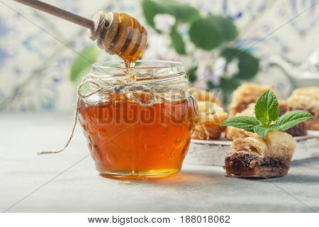 Honey, Falling From A Stick On A Glass Jar And Raditional Arabic Dessert.