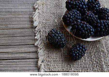 Ripe blackberries in a ceramic bowl on burlap cloth on old wooden background.Blackberry.Healthy food or diet concept.