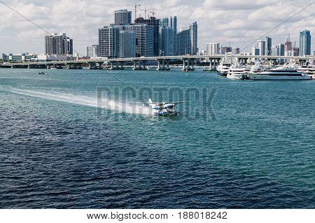 A Small Seaplane Taxiing Past Miami Bridge