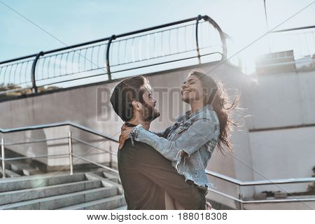 Love is in the air. Handsome man carrying young attractive woman while spending time outdoors