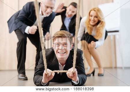 Great fun. Cheerful nice handsome man lying on the floor and holding the rope while having fun with his colleagues