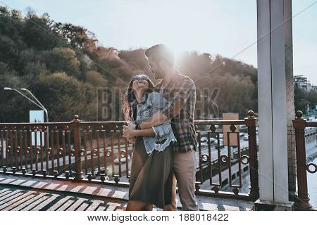 Romantic moment. Handsome man embracing young attractive woman while standing on the bridge outdoors