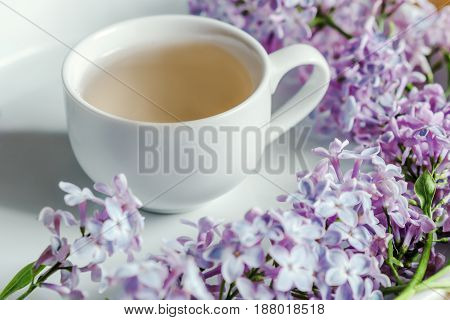 Springtime. Cup Of Tea And Lilac Morning Bouquet On The Table.  White Background.
