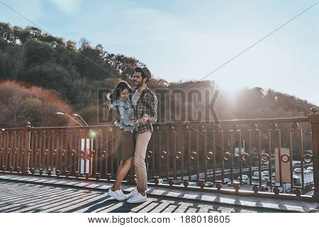 Simply in love. Full length of beautiful young couple dancing while standing on the bridge outdoors