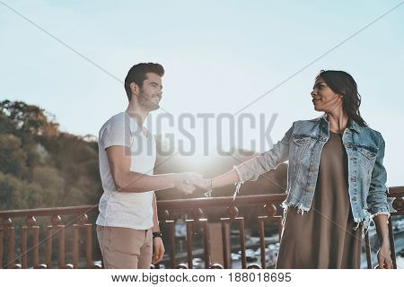 She is the one for him. Beautiful young couple holding hands and smiling while standing on the bridge outdoors