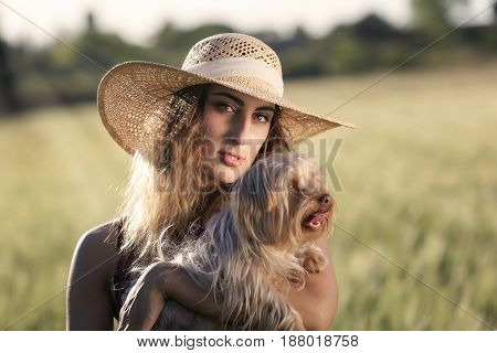 Blonde girl outdoors. With hat and white dress in the wheat field. Backlit.